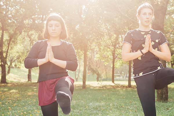 graphicstock two young beautiful caucasian women stretching outdoor in a city park in sunny day sportive training yoga concept B6XB6oYk 1 2